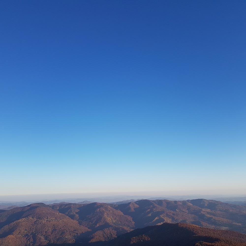 Vedere panoramica la apus de soare peste Muntii Siriu catre Ciucas
